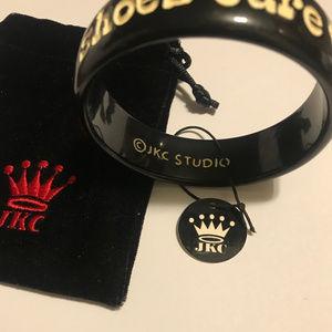 JKC STUDIO BANGLE BLACK W/ WHITE LETTERING NWT